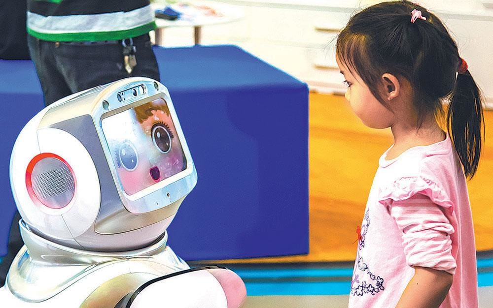 An AI powered robot interacts with a child at a tech and innovation expo in Nanjing, China. (China Daily)