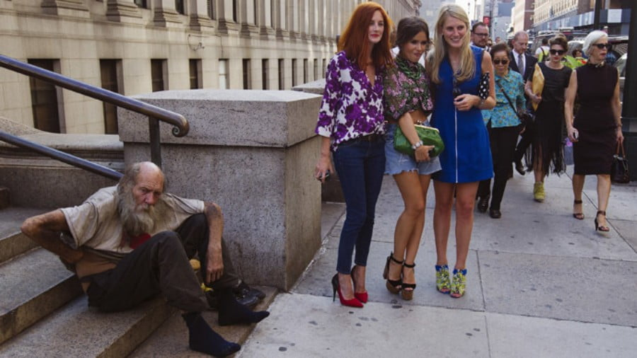 Fashionistas pose for photographs in front of a homeless man outside Moynihan Station following a showing of the Rag & Bone Spring/Summer 2013 collection during New York Fashion Week (Reuters/Lucas Jackson) / Reuters
