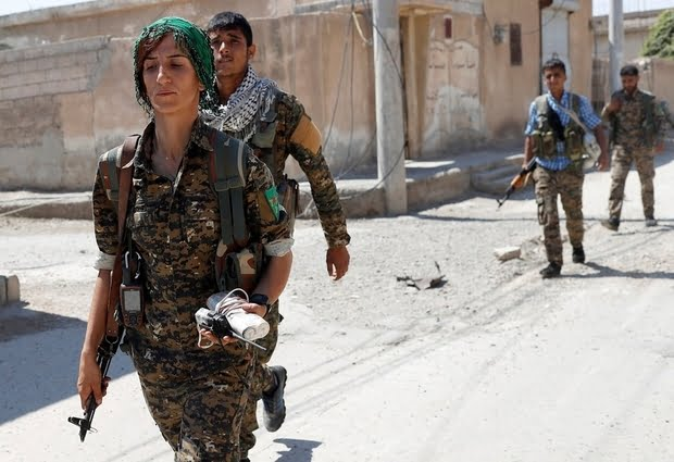 Sheen Ibrahim, Kurdish fighter from the People's Protection Units (YPG) walks together with other  YPG fighters in Raqqa