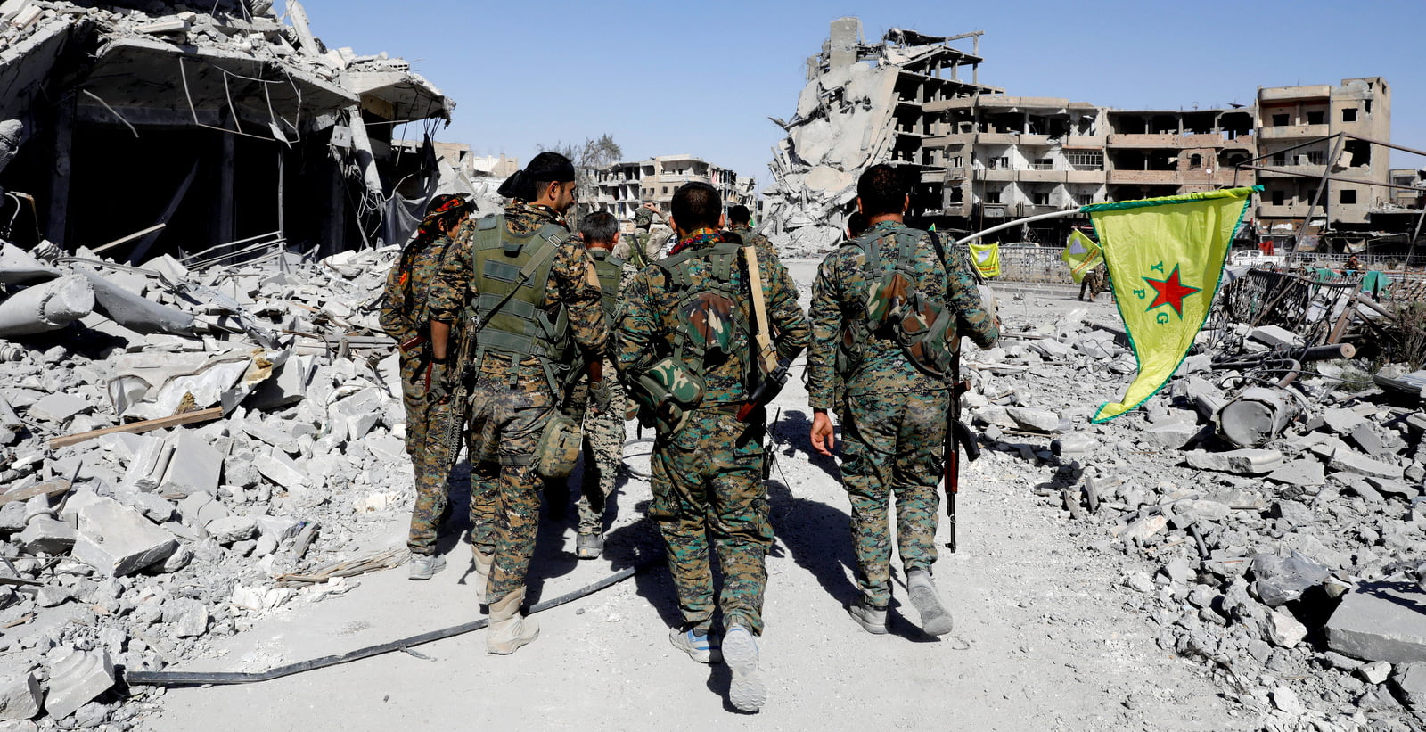 Syrian Democratic Forces Fighters walk past the ruins of destroyed buildings near the National Hospital after Raqqa was liberated from the Islamic State (ISIS), in Raqqa, Syria October 17, 2017. (Erik De Castro/Reuters)