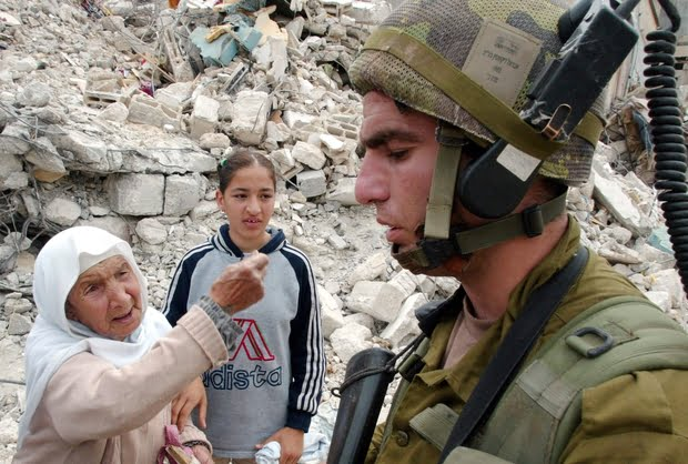 A Palestinian woman argues with an Israeli soldier in the Jenin refugee camp in the northern West Ba..