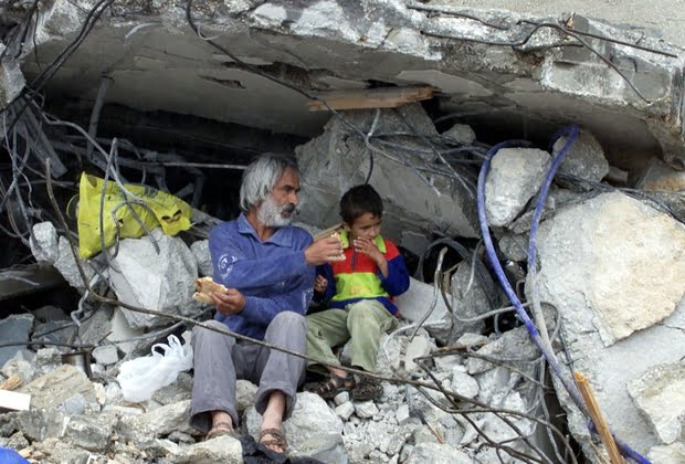PALESTINIAN GIVES BREAD TO A BOY IN THE REMAINS OF THEIR HOME IN JENINREFUGEE CAMP.
