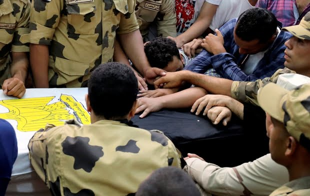 Family members attend the funeral of officer Khaled al-Maghrabi, who was killed during a suicide bomb attack on an army checkpoint in Sinai in his hometown Toukh, El-Kalubia governorate, northeast of Cairo
