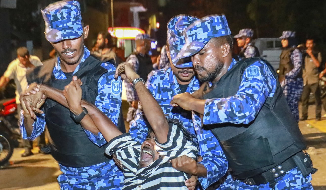 Maldivian police officers detain an opposition protester demanding the release of political prisoners during a protest in Male, Maldives. Photo: AP