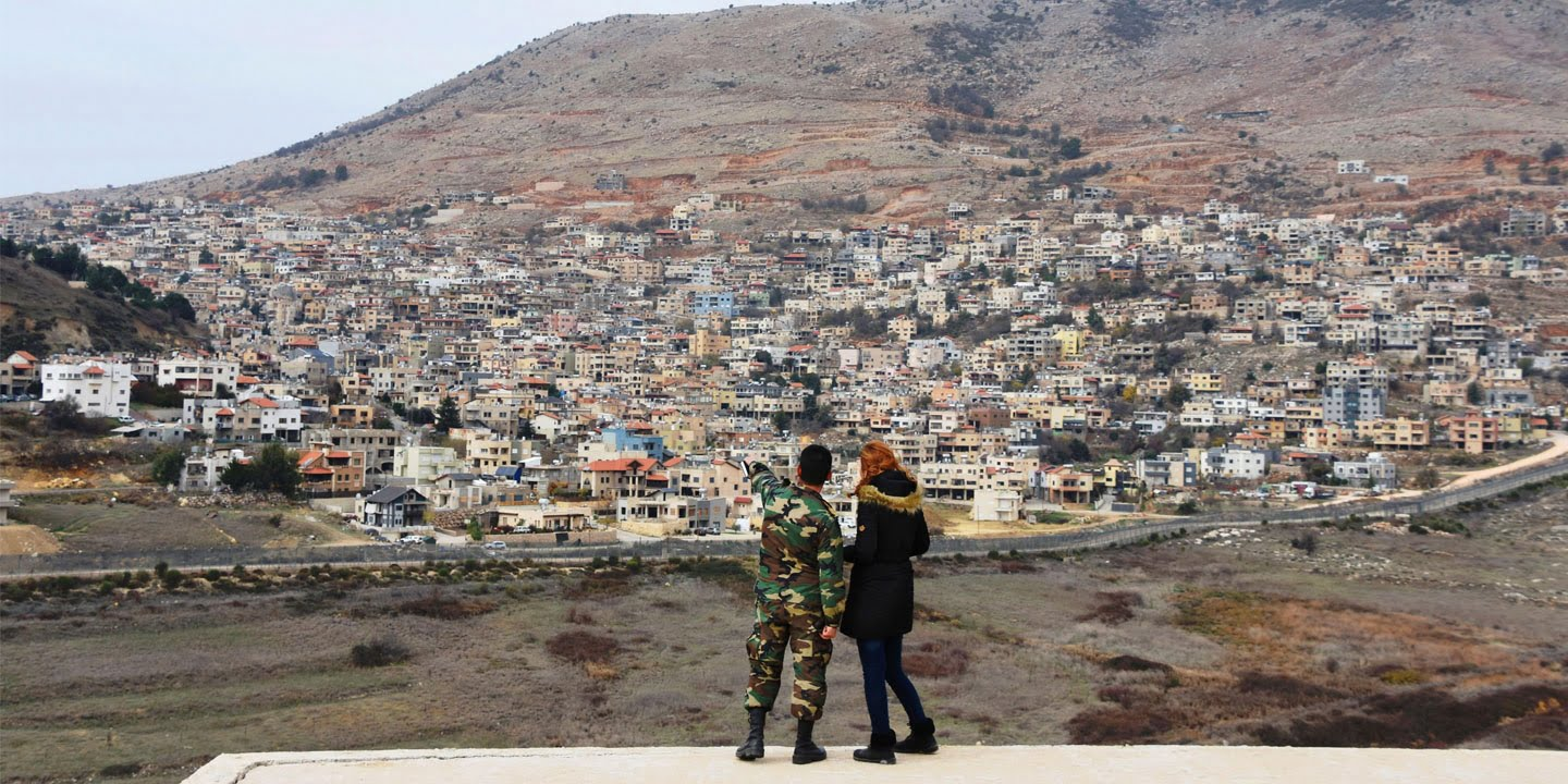 A Syrian military spokesperson (L) points to the Israeli-occupied Golan Heights on Dec. 23, 2017, in Al Gunaytirah in southwestern Syria. (Kyodo via AP Images)