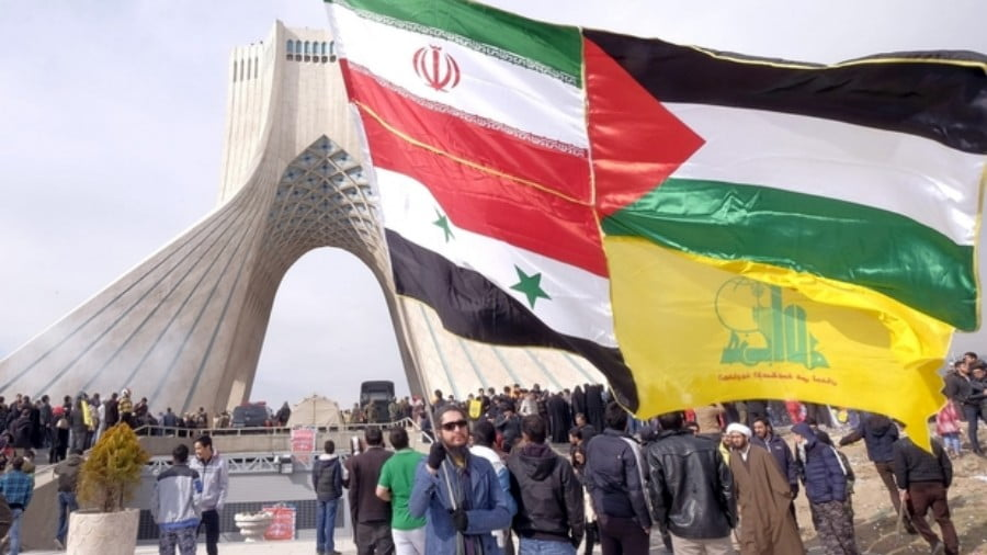 A man carries a giant flag made of flags of Iran, Palestine, Syria and Hezbollah, during a ceremony marking the 37th anniversary of the Islamic Revolution, in Tehran 11 February, 2016 (REUTERS)