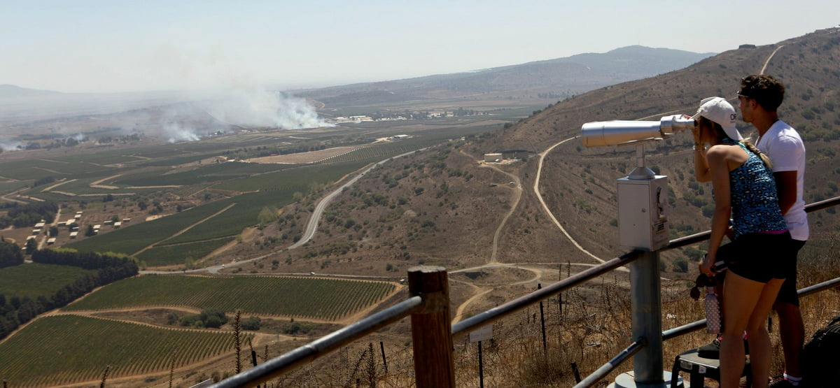 Israeli tourists watch smoke rising near the Syrian border of the occupied Golan Heights as the Syrian army fights to regain control of the Quneitra border crossing from rebel groups, thought to be covertly supported by the Israeli government. (Atef Safadi/EPA)
