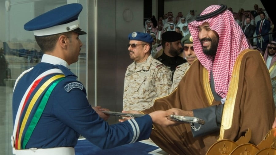 A cadet at King Faisal Air Academy receives a sword from Saudi Arabia's Crown Prince Mohammed bin Salman during a graduation ceremony in Riyadh, Saudi Arabia, on 21 February 2018 (Reuters)