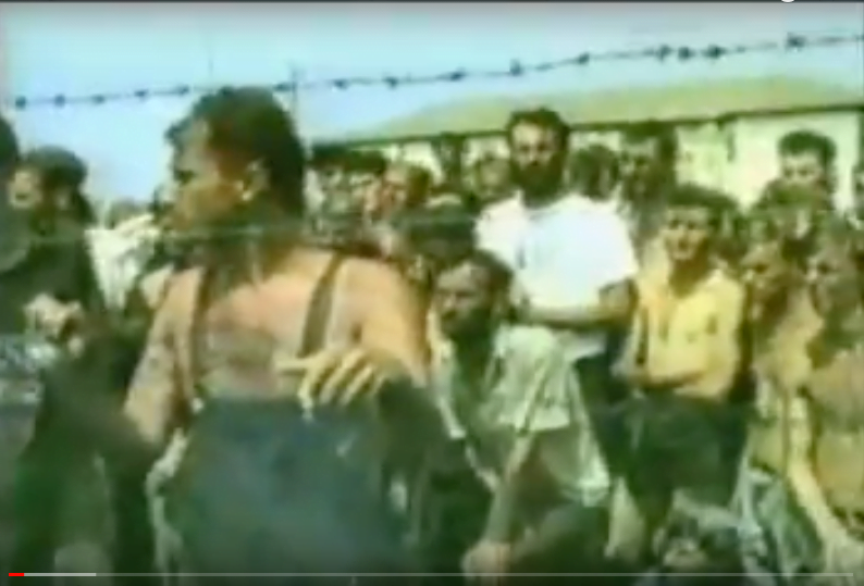 """screen cap from the documentary """"Judgement!"""" exposing the blatant fakery involved in portraying the so-called """"Serbian death camps"""" These men are not imprisoned behind barbed wire, they are standing outside a wired-off storage area from inside of which the crew are filming. Compare with some of the implausible footage we have been shown lately of alleged White Helmet rescue operations and other dubious-looking heroics."""