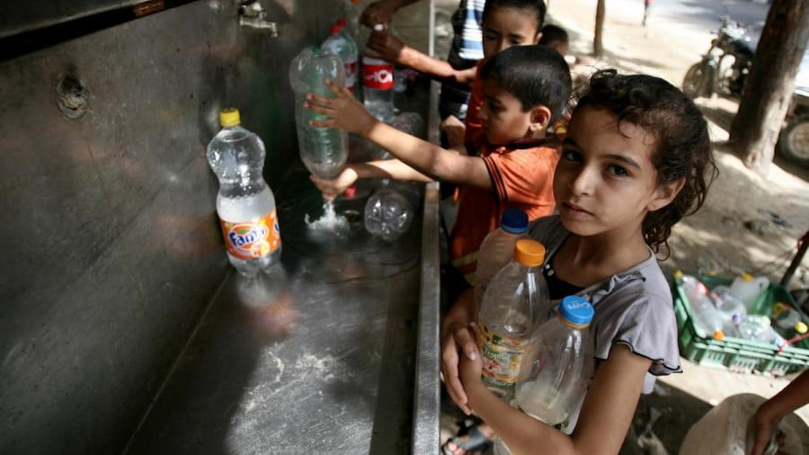 Palestinian children fill their bottles with water from a UNICEF tap in Rafah in the southern Gaza Strip. (Photo: UNICEF)
