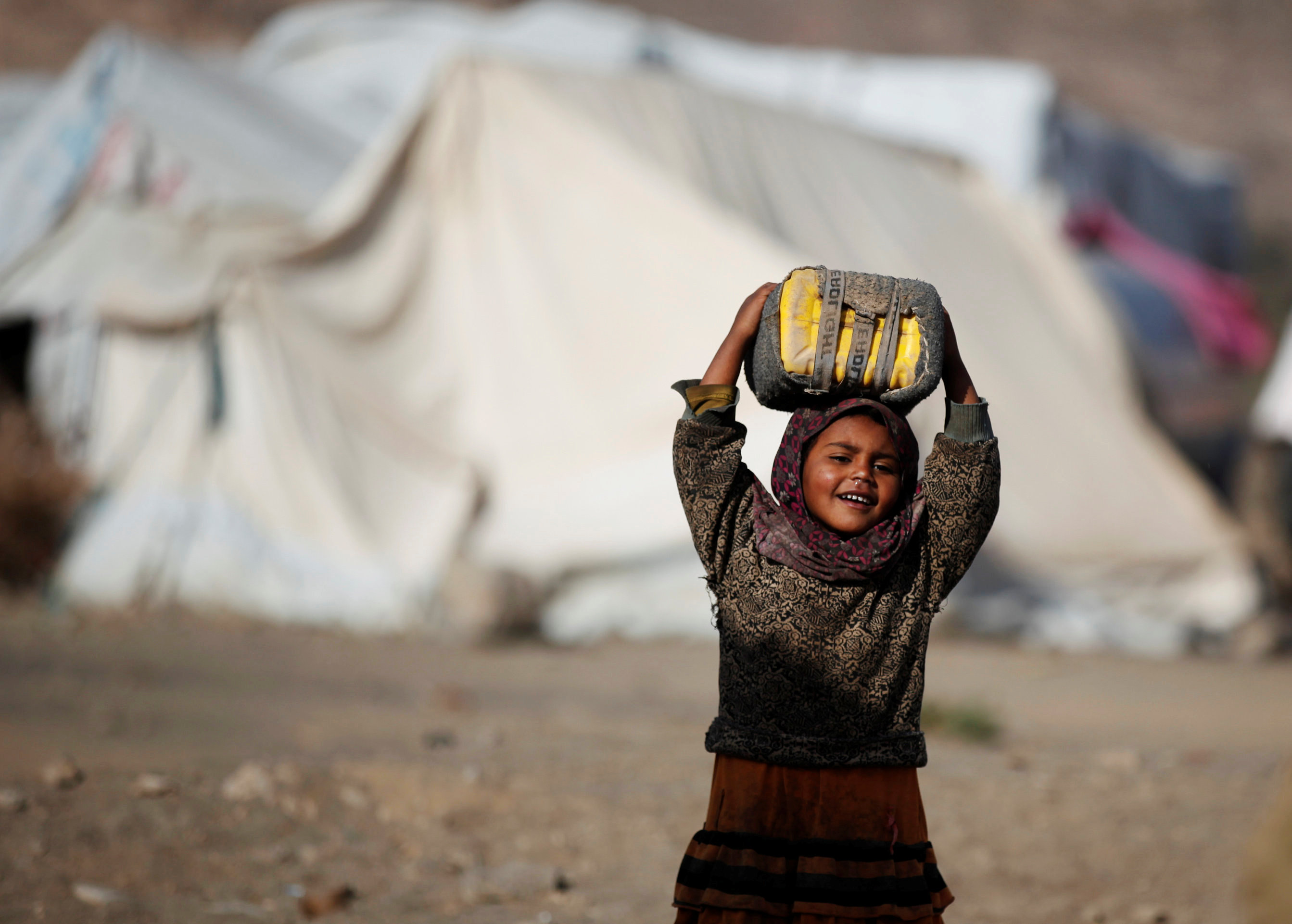 A girl carries a can to fill it up with water at a camp for internally displaced people in Dharawan, near the capital Sanaa
