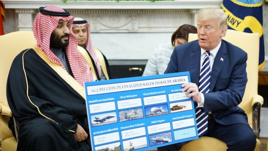 US President Donald Trump (right) holds a defence sales chart with Saudi Arabia's Crown Prince Mohammad bin Salman in the Oval Office of the White House on March 20, 2018 in Washington DC. Photo: AFP/ Mandel Ngan