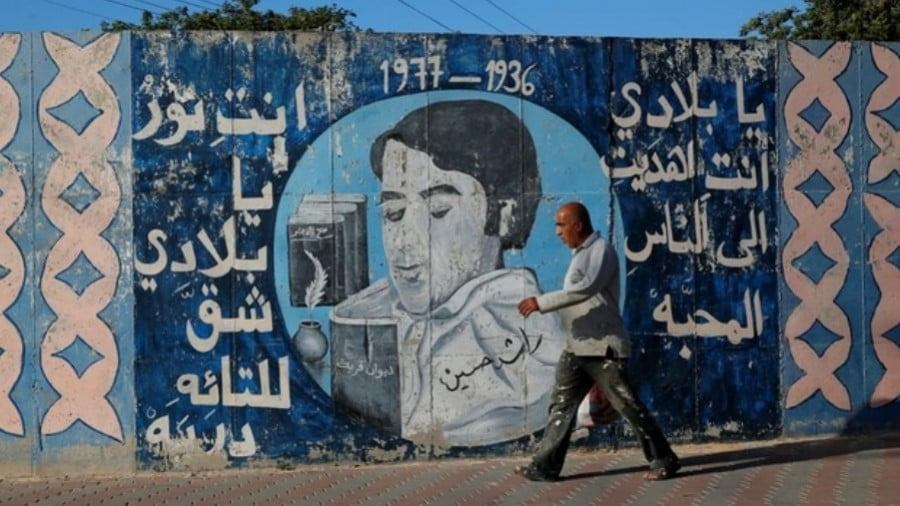"""A man walks past an Umm al-Fahm mural that reads: """"My country, you gave us love and light which revealed paths for the lost"""" (Reuters)"""