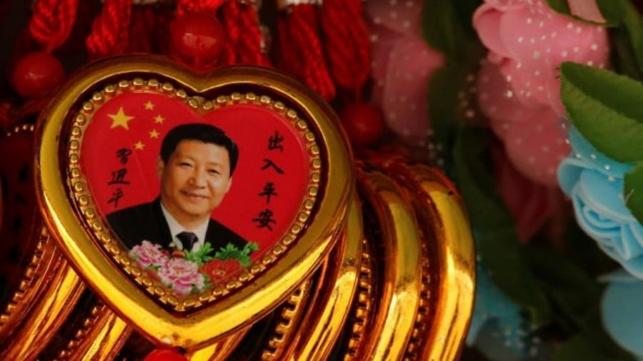 Souvenir necklaces with a portrait of Chinese President Xi Jinping are displayed for sale at a stall in Tiananmen Square in Beijing on February 26, 2018. Photo: Reuters/Thomas Peter