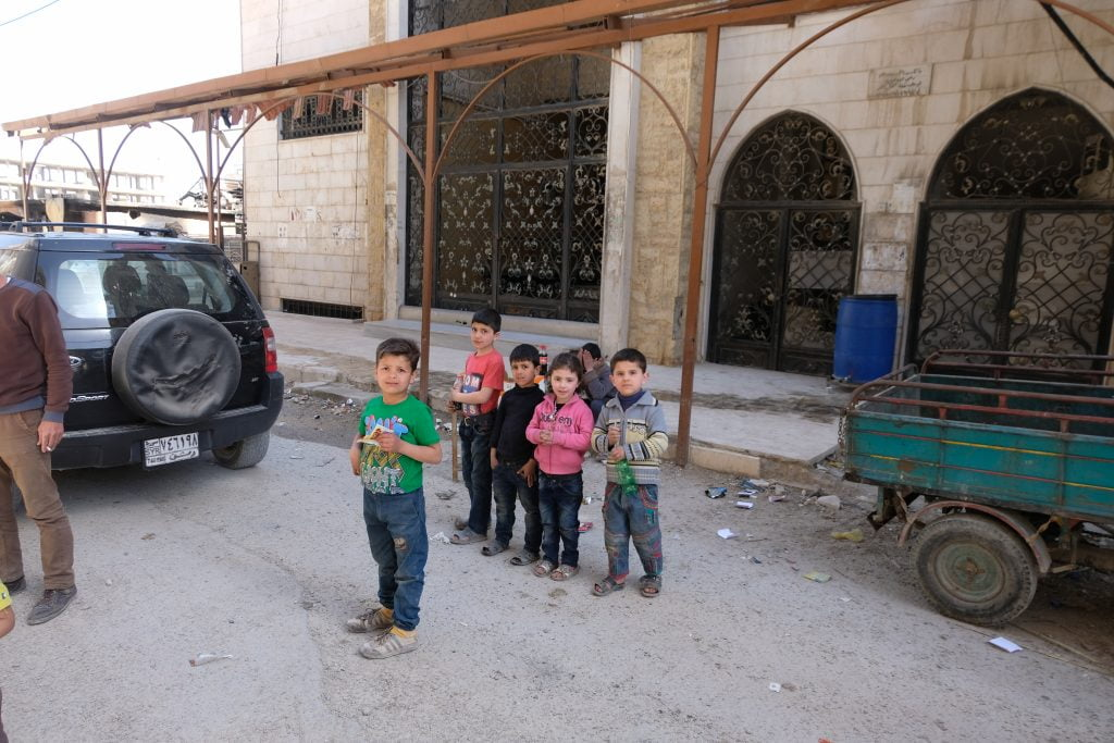 Children stand next to the entrance to a chemical weapons manufacturing centre in Erbin, Eastern Ghouta. (Photo: Vanessa Beeley)