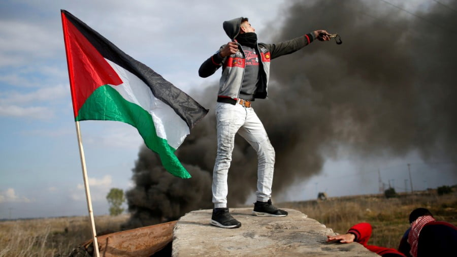 A Palestinian demonstrator uses a slingshot to hurl stones towards Israeli troops during clashes at a protest against U.S. President Donald Trump's decision to recognize Jerusalem as the capital of Israel, near the border with Israel in the east of Gaza City December 15, 2017. REUTERS/Mohammed Salem