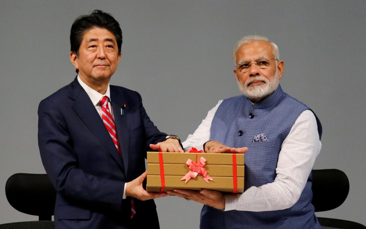 Japanese Prime Minister Shinzo Abe and his Indian counterpart Narendra Modi hold a replica of a brick during the India-Japan Annual Summit, in Gandhinagar