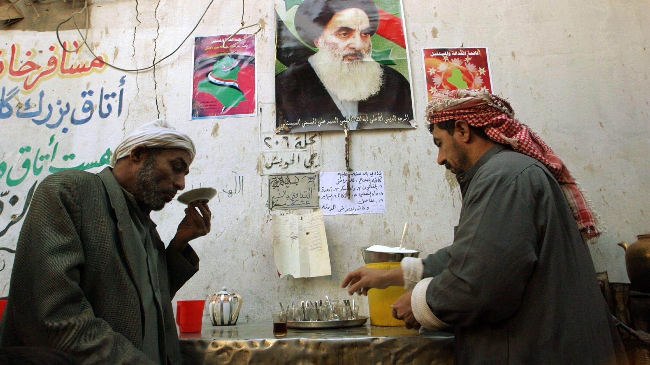 Men sit under poster of Shi'ite leader Sistani as they drink tea in Najaf.