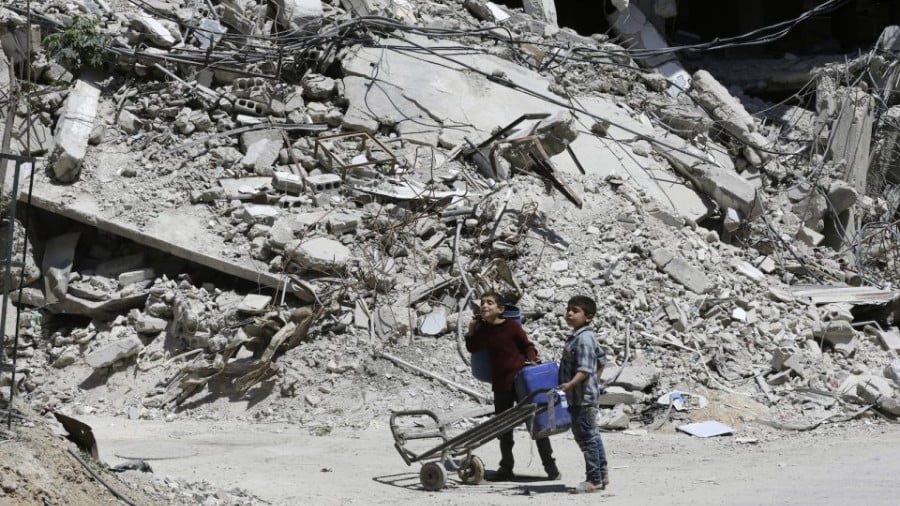 Syrian boys walk along a destroyed street in Douma on the outskirts of Damascus on April 16. Photo: AFP/Louai Beshara