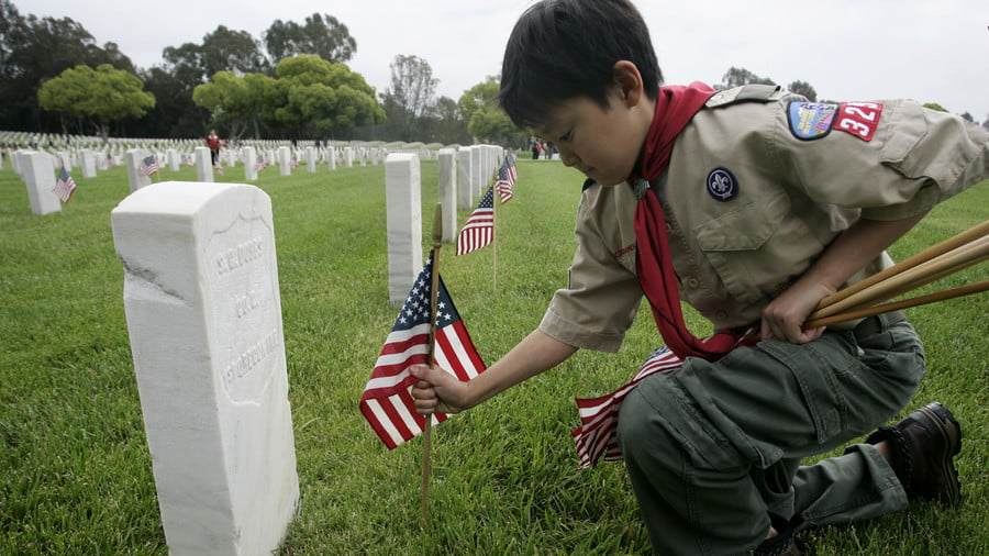 Boy Scout places a flag at a gravesite of a US military veteran © Jonathan Alcorn / Reuters