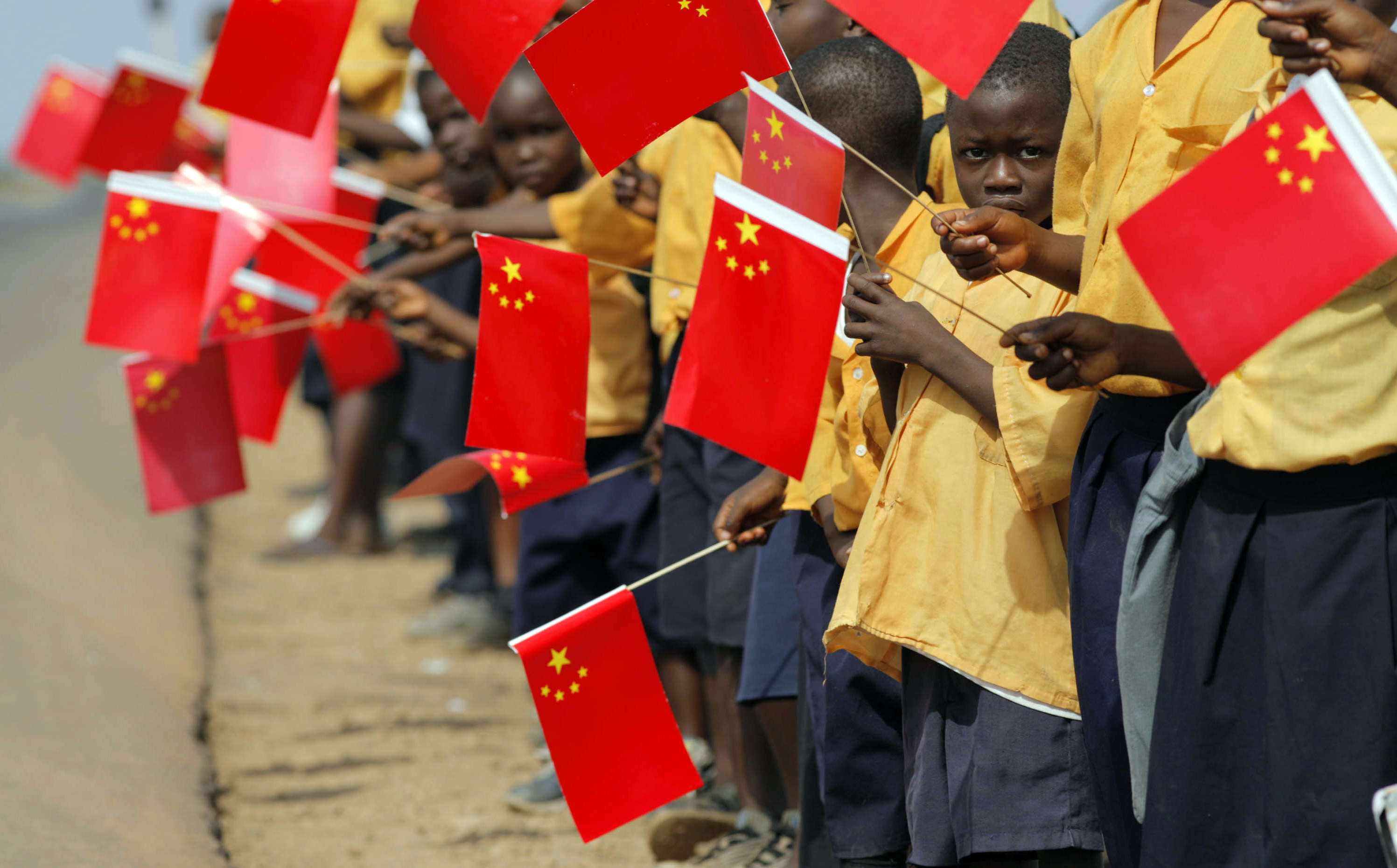 Liberian children hold Chinese flags before the arrival of China's President Hu in Monrovia
