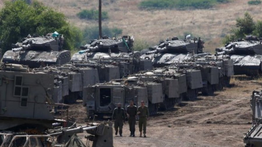 Israeli soldiers walk past armored vehicles in the Israeli-occupied Golan Heights on May 10, 2018. Photo: Reuters/Ronen Zvulun
