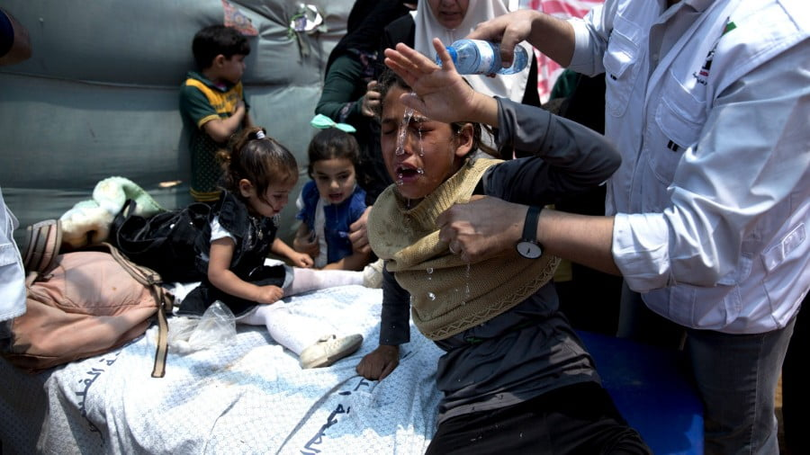 Medics treat Palestinian children suffering from teargas inhalation during a protest near Beit Lahiya, Gaza Strip, May 14, 2018. Israeli soldiers shot and killed dozens of Palestinians during mass protests along the Gaza border on Monday. It was the deadliest day there since a devastating 2014 cross-border war and cast a pall over Israel's festive inauguration of the new U.S. Embassy in contested Jerusalem. (AP/Dusan Vranic)