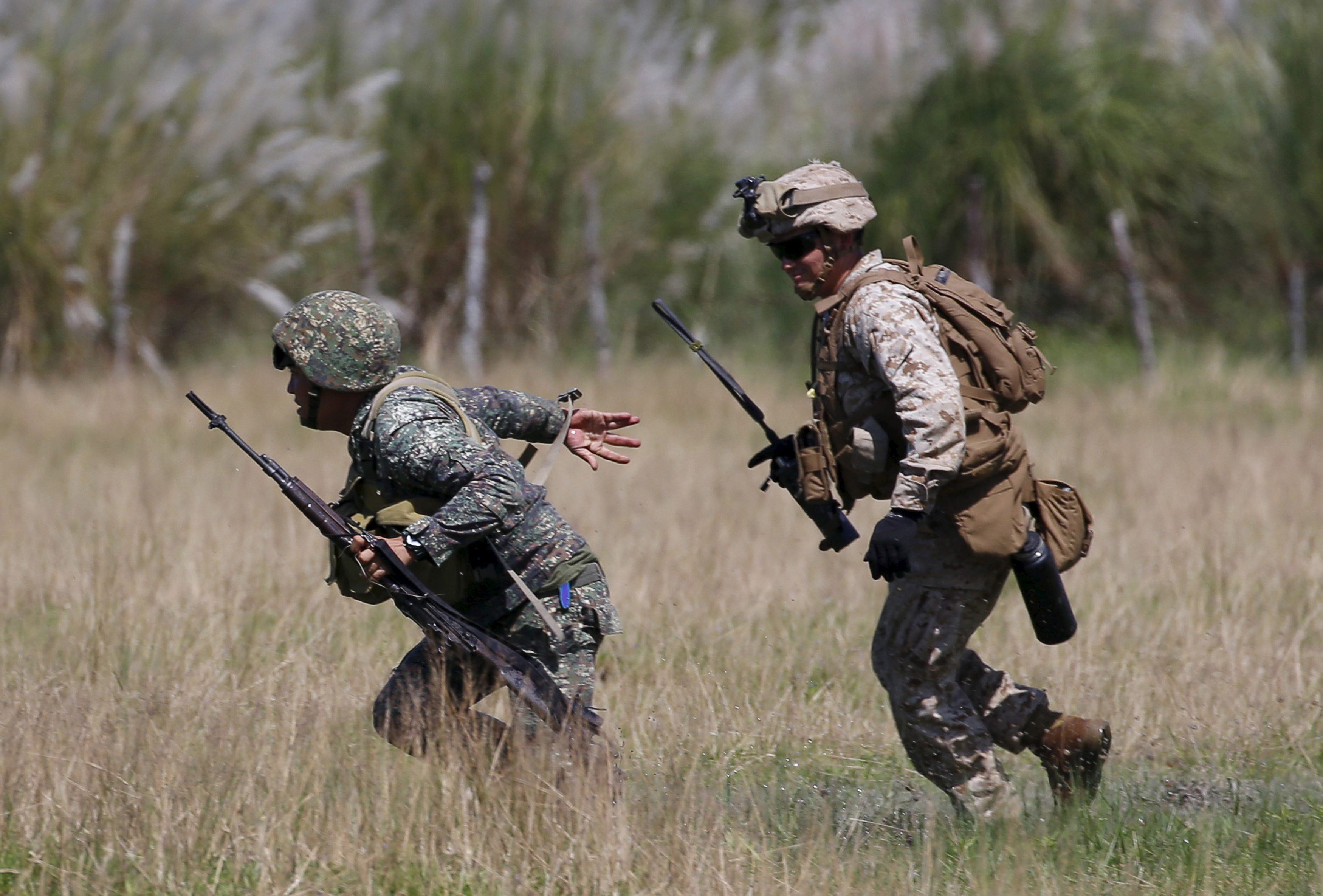 A U.S. Marine from the 3rd Marine Expeditionary Brigade runs with a Philippine soldier during assault exercises in joint drills aimed at enhancing cooperation between the allies at a Philippine Naval base San Antonio