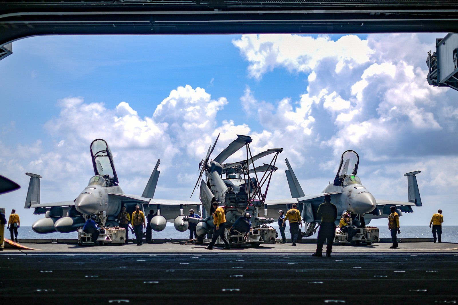 U.S. Navy sailors move aircraft from an elevator into the hangar bay of the aircraft carrier USS Theodore Roosevelt in the South China Sea