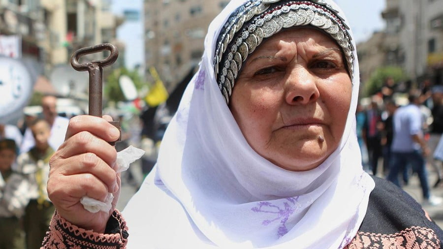 Palestinian woman holds a key, symbolising the right to her home from 1948, during the 68th anniversary of the 'Nakba' in Ramallah, West Bank