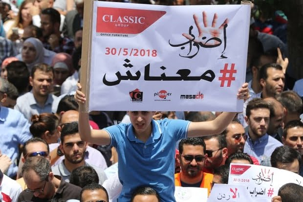 Thousands of Jordanians take to the streets of Amman on 30 May 2018 to protest against a new income tax draft law which was approved by the government. Arabic slogan on poster placard reads: 'Strike/We are broke' (AFP)