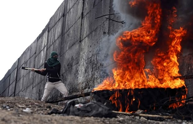 a20palestinian20protester20tries20to20hammer20a20hole20through20the20israeli20barrier20that20separates20the20west20bank20town20of20abu20dis20from20jerusalem2c20during20clashes