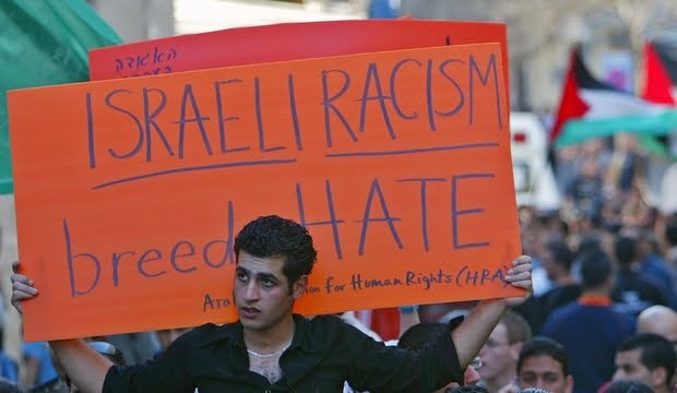 Israeli Arab youth holds sign during demonstration near Roman Catholic Church in Nazareth