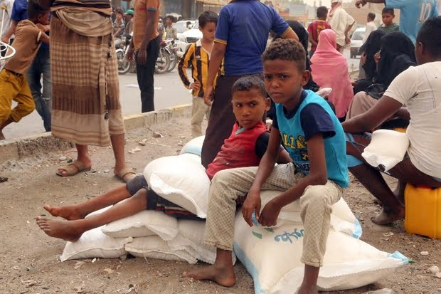 Yemeni children receive food aid in the coastal city of Hodeidah on 14 June 2018 (AFP)