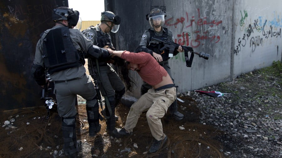 Israeli border police drag an activist by the hair next to Israel's apartheid wall during a protest in the occupied West Bank village of Bil'in, March 2, 2018. Palestinian protesters and foreign activists marched to commemorate the 13th anniversary of the ongoing weekly protests against the Israeli apartheid wall and Jewish-only settlements in Bil'in. Nasser Nasser | AP