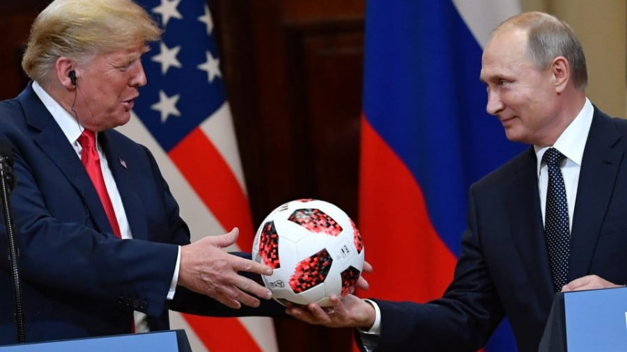 Russian President Vladimir Putin, right, offers a ball from the 2018 football World Cup to US President Donald Trump during their joint press conference after a meeting at the Presidential Palace in Helsinki, on July 16, 2018. Photo: AFP/ Yuri Kadobnov