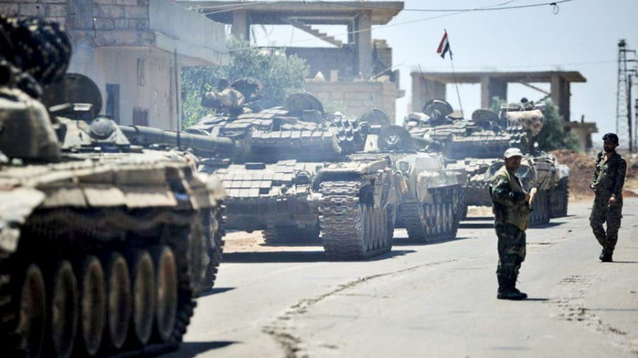 Syrian government tanks and soldiers take positions in the town of Western Ghariyah, about 15km east of the southern embattled city of Daraa. Photo: AFP/ SANA handout released on June 30, 2018.