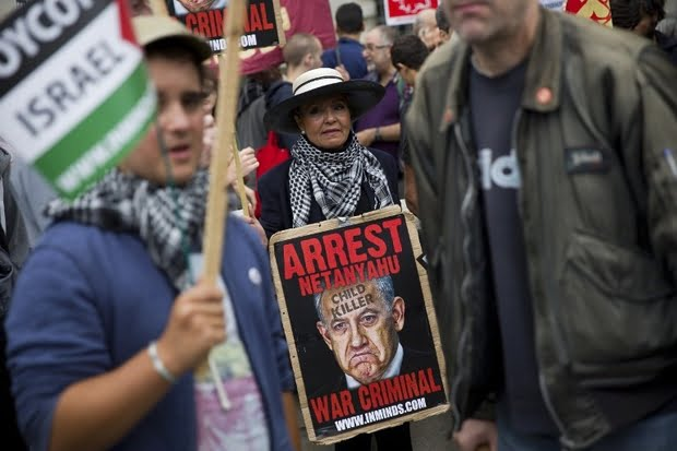 A pro-Palestinian demonstrator carrying a placard depicting Israeli Prime Minister Benjamin Netanyahu joins others during a protest outside the gates of Downing Street in London on 9 September, 2015 (AFP)