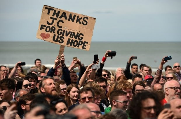 Supporters of Britain's main opposition Labour Party hold placards as the leader Jeremy Corbyn speaks during a campaign visit in Colwyn Bay, north Wales on 7 June, 2017 (AFP)