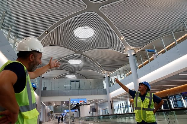 Workers chat at the international terminal of the city's new airport under construction in Istanbul