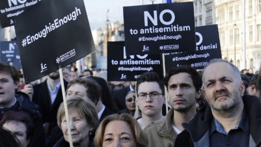 Members of the Jewish community hold a protest against Britain's opposition Labour party leader Jeremy Corbyn and anti-semitism in the Labour party, outside the British Houses of Parliament in central London on 26 March, 2018 (AFP)