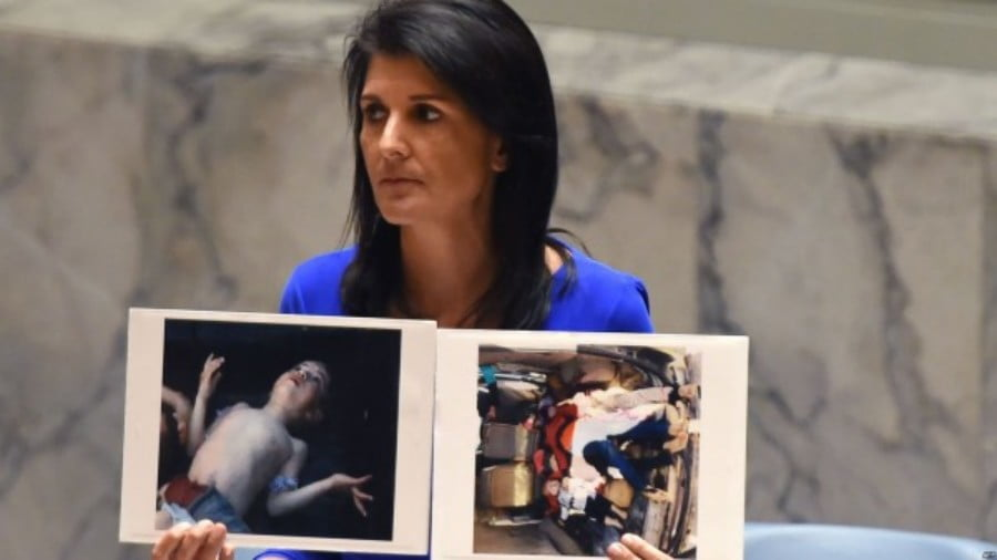 U.S. Ambassador to the UN Nikki Haley holds photos of victims of the Syrian gas attack as she speaks as the UN Security Council, April 2017