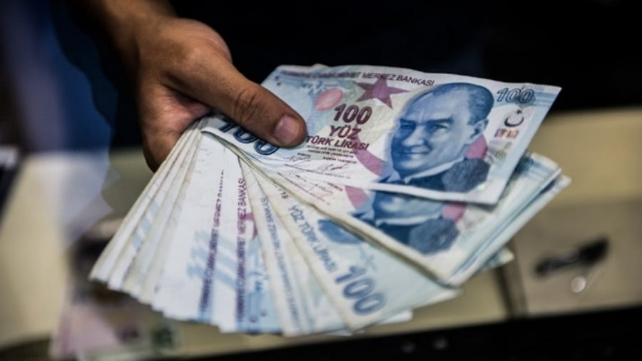 A teller holds Turkish lira banknotes at a currency exchange office in August 2018 (Yasin AKGUL / AFP)