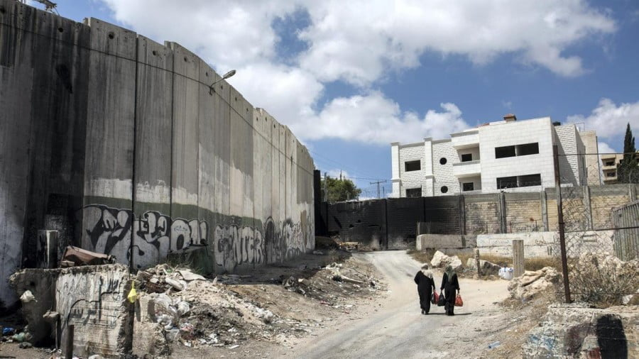 Palestinian women walk beneath Israel's separation barrier on August 27, 2018. Heidi Levine for The National