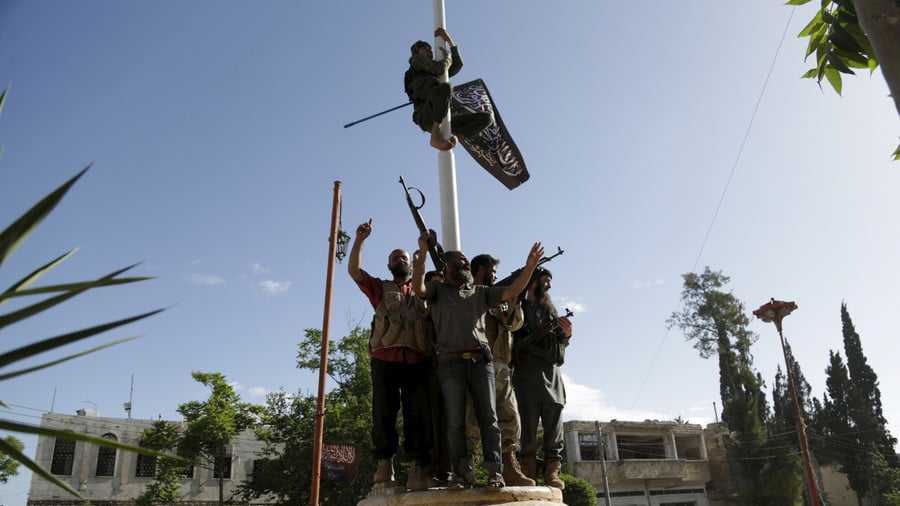 A member of al Qaeda's Nusra Front climbs on a pole to hang the Nusra flag after a coalition of insurgent groups seized the area in Idlib province, May 29, 2015 © Khalil Ashawi / Reuters