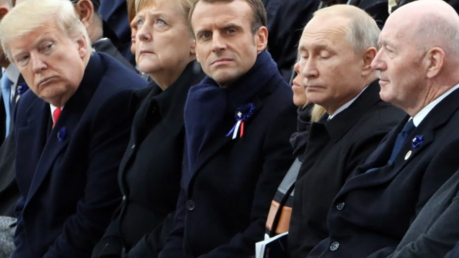 US President Donald Trump peers across from German Chancellor Angela Merkel toward French President Emmanuel Macron and his wife Brigitte, Russian President Vladimir Putin and Australian Governor General Peter Cosgrove at a ceremony to mark the 100th anniversary in Paris of the end of World War I. Photo: AFP