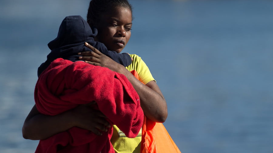 A migrant woman holds a baby upon her arrival aboard a coast guard boat at Malaga's harbour on September 23, 2018 © Jorge Guerrero / AFP