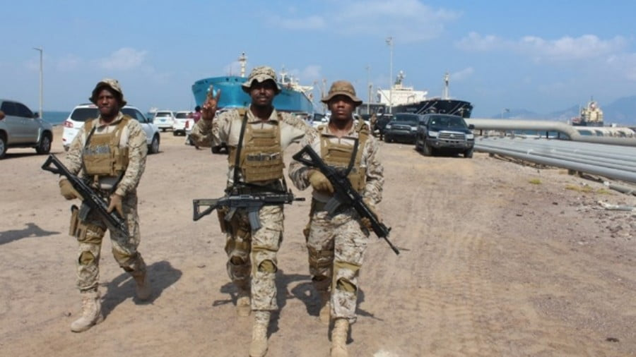 Soldiers loyal to Saudi-led coalition forces gesture as they guard ships docked in the southern Yemeni port of Aden on 29 October 2018 (AFP)