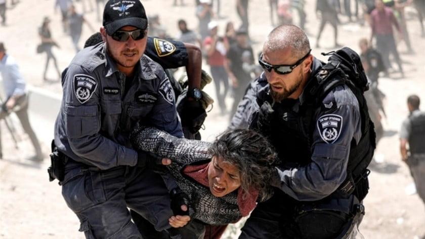 Israeli policemen detain a Palestinian girl in Khan al-Ahmar, West Bank on 4 July 2018 (Reuters)