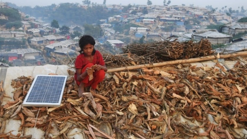 A young Rohingya refugee spreads out firewood to dry on the roof of a shack in Bangladesh's Cox's Bazar district on 18 November (AFP)